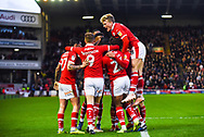 Kieffer Moore of Barnsley (19) scores a goal and celebrates to make the score 2-0, Cameron McGeehan of Barnsley (8) jumps on to a huddle of celebrating players, during the EFL Sky Bet League 1 match between Barnsley and Bradford City at Oakwell, Barnsley, England on 12 January 2019.