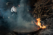 Indigenous Purepecha workers places a copper pan on an open forge to begin the process of hardening and forming the pan at a copper workshop in Santa Clara del Cobre, Michoacan, Mexico. The Purepecha people have been crafting copper crafts since the 12th century.