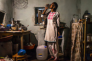 Cheekata  Srujana, 18, drinks a cup of water as she waits for a meal to cook in her kitchen in Peddapur, a remote village in Warangal, Telangana, India, on 22nd March 2015. Cheekata only uses safe water for all her cooking and drinking needs of the family. Photo by Suzanne Lee/Panos Pictures for Safe Water Network