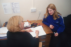 Pregnant teenage girl sitting at desk in GP surgery talking to female doctor,