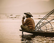 Thoughtful fisherman taking a smoke on Lake Inle, Myanmar
