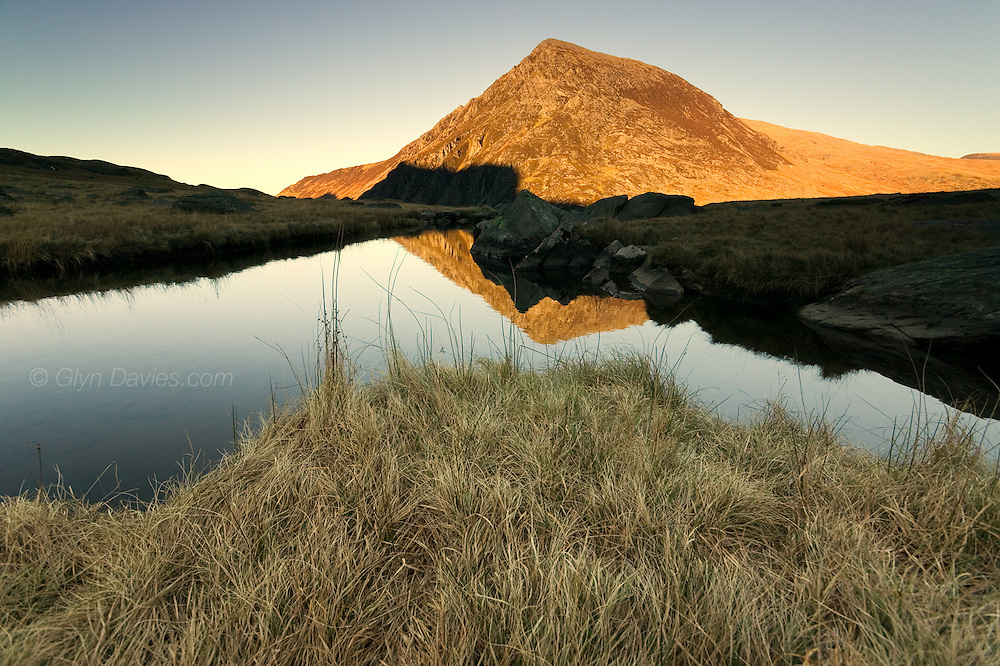 The pointed peak of Pen yr Ole Wen, the first peak of the Carneddau range in Snowdonia, in evening sunlight, reflected in a slow moving, dark, river pool, flowing out of Cwm Idwal hanging valley down to the Ogwen Falls and the Nant Ffrancon pass .