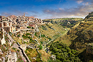 """Vew of """"la Gravina"""" ravine and the Sassi of Matera, Basilicata, Italy. A UNESCO World Heritage site.<br /> <br /> The area of Matera has been occupied since the Palaeolithic (10th millennium BC) making it one of the oldest continually inhabited settlements in the world. <br /> The town of Matera was founded by the Roman Lucius Caecilius Metellus in 251 BC and remained a Roman town until  was conquered by the Lombards In AD 664 becoming part of the Duchy of Benevento.  Matera was subject to the power struggles of southern Italy coming under the rule of the Byzantine Roman, the Germans and finally Matera was ruled by the Normans from 1043 until the Aragonese took possession in the 15th century. <br /> <br /> At the ancient heart of Matera are cave dwellings known as Sassi. As the fortunes of Matera failed the sassy became slum dwelling and the appalling living conditions became be the disgrace of Italy. From the 1970's families were forcibly removed from the Sassi and rehoused in the new town of Matera. Today tourism has regenerated Matera and the sassi have been modernised and are lived in again making them probably the longest inhabited houses in the world dating back 9000 years. .<br /> <br /> Visit our ROMAN ART & HISTORIC SITES PHOTO COLLECTIONS for more photos to download or buy as wall art prints https://funkystock.photoshelter.com/gallery-collection/The-Romans-Art-Artefacts-Antiquities-Historic-Sites-Pictures-Images/C0000r2uLJJo9_s0<br /> .<br /> <br /> Visit our MEDIEVAL PHOTO COLLECTIONS for more   photos  to download or buy as prints https://funkystock.photoshelter.com/gallery-collection/Medieval-Middle-Ages-Historic-Places-Arcaeological-Sites-Pictures-Images-of/C0000B5ZA54_WD0s"""