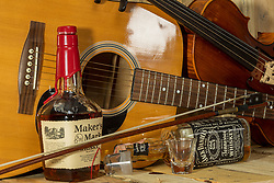Studio work with acoustic guitar, electric guitar, viola, fiddle, whiskey bottles, shot glasses and guitar pics on a rough wooden slat background.