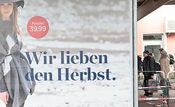 """14.10.2015, Bahnhof, Freilassing,GER, Flüchtlingskrise in der EU, im Bild Flüchtlinge warten auf dem Bahnsteig auf den Sonderzug vor einem Werbeplakat """"Wir lieben den Herbst, Poncho 39,99"""" // Refugees wait on the platform for the special train in front of a poster advertising """"We love the autumn, Poncho 39.99""""., Railway Station, Freilassing, Germany on 2015/10/14. EXPA Pictures © 2015, PhotoCredit: EXPA/ JFK"""