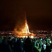 DERRY, NORTHERN IRELAND - MARCH 21, 2015: A crowd watches as a massive bonfire goes up in flames in Londonderry, Northern Ireland, March 21, 2015. Meant as a symbol of unity and overseen by a mostly American crew, the structure was built by youths from both Protestant and Catholic communities in Northern Ireland, where bonfires are a potent symbol of the region's tangled history of violence, religion and politics. CREDIT: Paulo Nunes dos Santos for The New York Times
