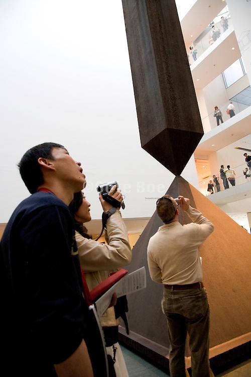 "people in the museum of Modern Art New York photographing the art works. Sculpture ""Broken Obelisk,"" by Barnett Newman,  1964."