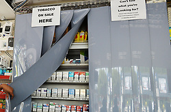 Embargoed to 2330 Monday July 31 File photo dated 7/8/2015 of a newsagent and tobacconist shop with the screens that cover all tobacco products. Tobacco firms are enticing Scottish retailers to promote their products despite a ban on the open display of cigarettes in shops, a new study has found.
