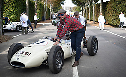 © licensed to London News Pictures. 12/09/2015<br /> Goodwood Revival Weekend, Goodwood, West Sussex. UK.<br /> The Goodwood Revival is the world's largest historic motor racing event. Competitors and enthusiasts dress in period fashions recreating the glorious days of the race circuit.<br /> Pictured. A 1958 Lotus Cooper Climax is pushed to the paddock in preparation for the next race.<br /> <br /> Photo credit : Ian Whittaker/LNP