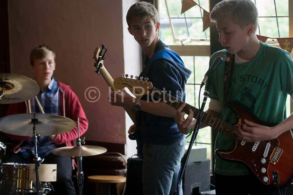 A teenage band of drums, bass and lead guitar perform in front of parents in an upstairs pub room in south London. 15 year-old lads play their own songs and covers by other musical artists. Looking over his shoulder, the bass player checks rhythm with the lead singer  and the drummer looks across his cymbals to ensure the tempo is right. The gig is a regular showcase organiused by their guitar teacher to demonstrate their musical skills as songwriters and musicians.