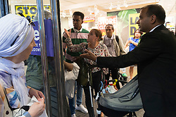 © Licensed to London News Pictures. 13/08/2016. Customer with grey hair and spectacles pushes his way past security staff into the store for a refund an he knocks into a mother with a pram and baby.  The mother gives the man verbal abuse. British Homes Stores Oxford Street Flagship store as it closes on its last day of trading. London, UK. Photo credit: Ray Tang/LNP