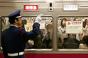 """Station attendand in front of the women-only car of KEIO line,  during the evening hours. In Tokyo, Wednesday 11 May, 2005.. In an attempt to combat the growing problem of gropers assaulting women in jam-packed trains, nine private railways and subway trains operated by the Tokyo metropolitan government introduced """"women only"""" cars Monday during the morning rush hour."""