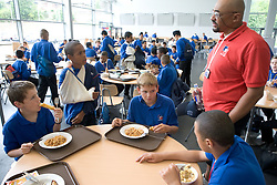 Physical Education teacher talking to Secondary School students in School Restaurant,