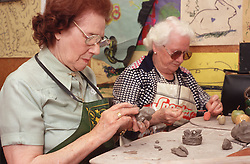 Two women with visual impairments learning pottery at the Institute for the Blind,