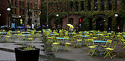 A passer-by's colorful umbrella complements the sea of vacant yellow chairs in Occidental Park.<br />
