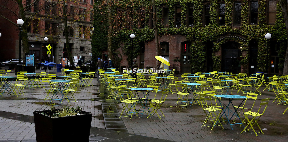 A passer-by's colorful umbrella complements the sea of vacant yellow chairs in Occidental Park.<br /> <br /> Alan Berner / The Seattle Times