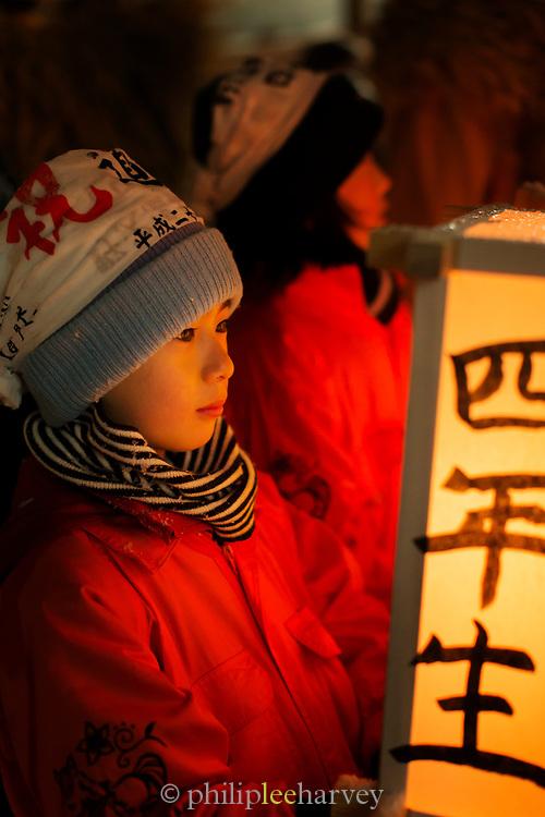 Child looking at illuminated lamp at night, Nozawaonsen, Japan