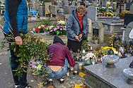 A family cares for a grave at Rakowicki cemetery in Krakow, Poland 2019.
