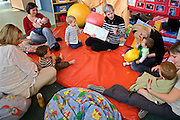 Mothers, staff and babies in the family centre at HMP Askham Grange sit in a circle listening to stories being read by a volunteer that visits the prison once a week. HMP/YOI Askham Grange is a women's open prison serving the Yorkshire area with a capacity of 128 women. It has extensive education, training and mother and Baby facilities.