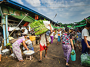 """25 OCTOBER 2015 - INSEIN, MYANMAR:  A man carries produce on his back through Danyin Market (also known as Da Nyin) in Insein, Myanmar, about 90 minutes from Yangon. Vendors in the market sell just about everything people in the area need, but mostly it's a """"wet market"""" with fruits, vegetables and meats. Most people in Myanmar still do not have refrigerators in their homes, so people go to market almost every day.    PHOTO BY JACK KURTZ"""