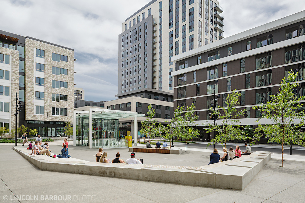 A good amount of people sit in a public, urban square.  Buildings surround the square.