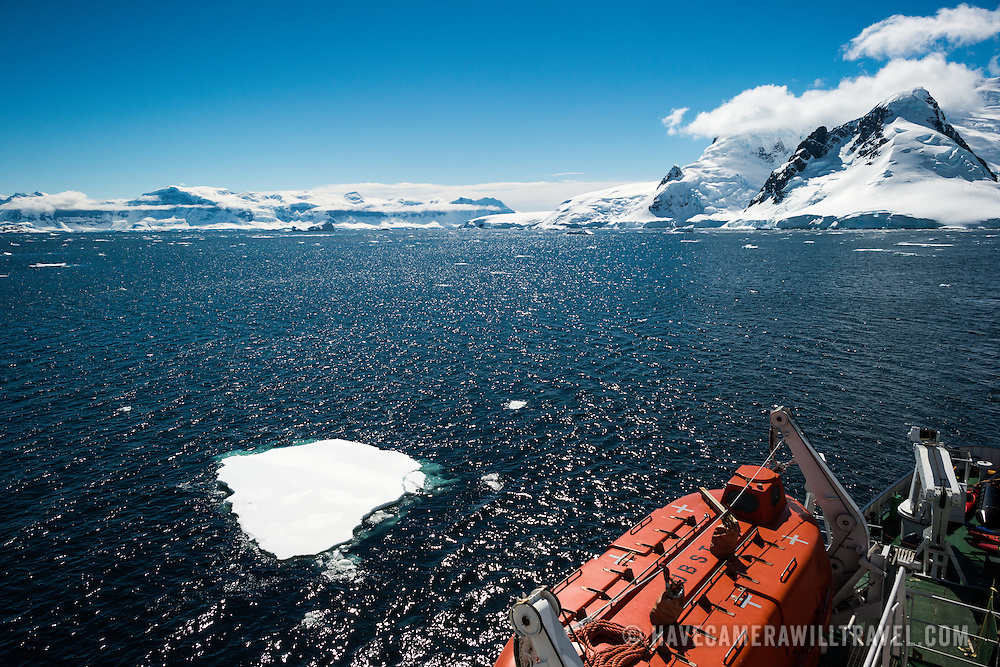 A cruise ship passes through a channel past small icebergs. In the foreground at bottom right of frame is one of the ship's lifeboats.
