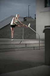 Mid adult woman stretching her leg on railing during dawn, Bavaria, Germany