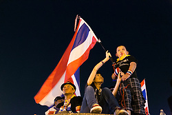 © Licensed to London News Pictures. 05/01/2014. A young child  waves the Thai flag from the top of the Victory Monument at a rally during the third day of the 'Bangkok Shutdown' as anti-government protesters continue with their 'shutdown' of Bangkok.  Major intersections in the heart of the city have been blocked in their campaign to oust Prime Minister Yingluck Shinawatra and her government in Bangkok, Thailand. Photo credit : Asanka Brendon Ratnayake/LNP