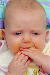 Closeup portrait of baby sucking fingers,