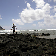 KAUAI, HI, July 15, 2007: A young hiker makes his way across Punahoa Point while hiking the Heritage Trail that runs along the South Shore's Poipu on the  island of Kauai in Hawaii. (Photograph by Todd Bigelow/Aurora)