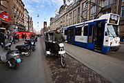 In Amsterdam passeert een fietstaxi op het Damrak een tram.<br /> <br /> In Amsterdam a bike taxi at the Damrak passes a tram.