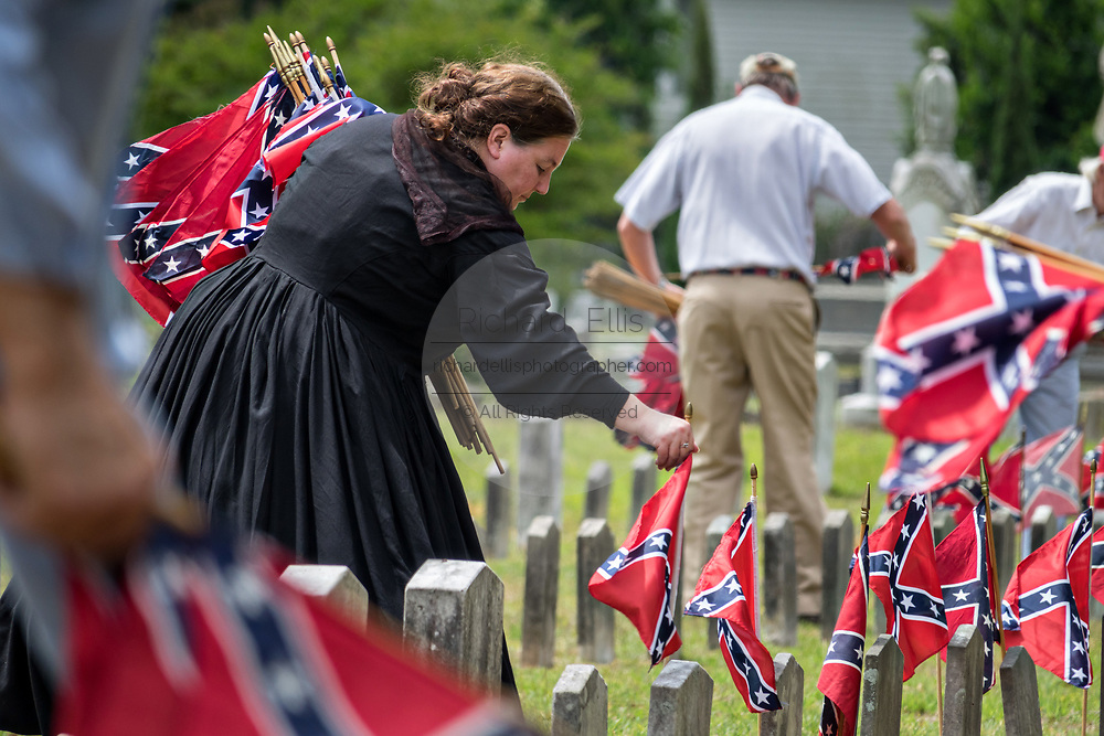 A member of the United Daughters of the Confederacy, dressed in period costume, collects battle flags from grave markers during Confederate Memorial Day at Magnolia Cemetery May 11, 2019 in Charleston, South Carolina. Confederate memorial day continues to be an official state holiday in South Carolina where the American Civil War began.