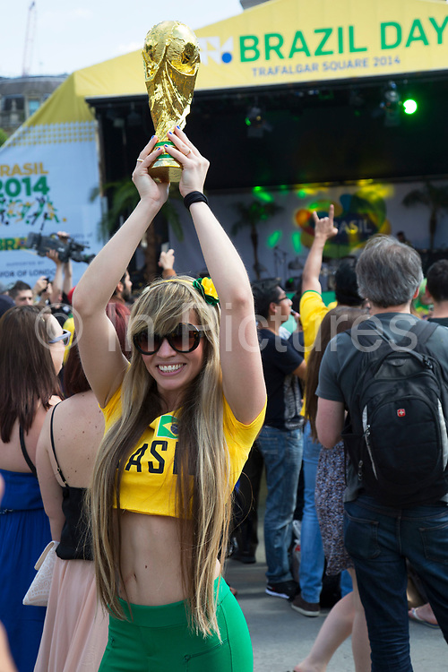 London, UK. Thursday 12th June 2014. Woman posing with a World Cup trophy. Brazilians gather for the Brazil Day celebrations in Trafalgar Sq. A gathering to celebrate the beginning of the Brazil 2014 FIFA World Cup. Revellers sing and dance and play football games and all in the yellow green and blue of the Brazilian flag.