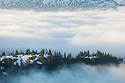 Low clouds shroud a forested ridge at the base of Damnation Peak, North Cascades National Park, Washington.