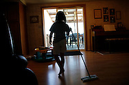 Hannah Jeub, 6, sweeps the floor in the family home in Monument, Colorado July 17, 2009. Quiverfull believers Wendy and Chris Jeub have 15 children and would be happy to have more if God wills it they say. REUTERS/Rick Wilking (UNITED STATES)