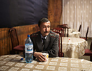 Police sitting and relaxing at a restaurant.<br /> <br /> The town of Khorog (2200m), is the capital of the Gorno-Badakhshan Autonomous Province (GBAO) in Tajikistan. It is situated in the Pamir Mountains (ancient Mount Imeon) at the confluence of the Gunt and Panj rivers.<br /> The city is bounded to the south and to the north by the deltas of the Shakhdara and Gunt rivers, respectively. The two rivers merge in the eastern part of the city flow through the city, dividing it almost evenly until its delta in the river Panj, also being known as Amu Darya, or in antiquity the Oxus on the border with Afghanistan. Khorog is known for its beautiful poplar trees that dominate the flora of the city.<br /> Khorog is one of the poorest areas of Tajikistan, with the charitable organization Aga Khan Foundation providing almost the only source of cash income. Most of its inhabitants are Ismaili Muslims.<br /> <br /> Tajikistan, a mountainous landlocked country in Central Asia. Afghanistan borders it to the south, Uzbekistan to the west, Kyrgyzstan to the north, and People's Republic of China to the east. Tajikistan also lies adjacent to Pakistan separated by the narrow Wakhan Corridor.<br /> Tajikistan became a republic of the Soviet Union in the 20th century, known as the Tajik Soviet Socialist Republic.<br /> It was the first of the Central Asian republic to gain independence in December 1991.