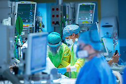 © Licensed to London News Pictures . 11/02/2021. Wythenshawe , UK . Clinicians provide care to a patient on the ward . Covid positive patients are treated for the effects of Coronavirus in Wythenshawe's Intensive Care Unit . Photo credit : Joel Goodman/LNP