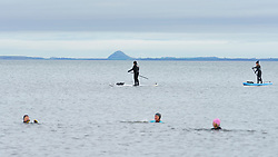 Portobello, Scotland, UK. 10 January 2020. Despite a national lockdown currently enforced in Scotland, Portobello promenade and beach was busy with large numbers of people spending Sunday afternoon there. Several police patrols were evident mostly keeping low key but officers spoke to cafe owners to urge them to keep correct social distancing between customers. Pic; Open water swimmers and paddle boarders . Iain Masterton/Alamy Live News