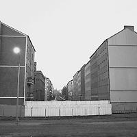 Eine Straßenschlucht, aufgrund der vielen geparkten Autos vermutlich in Richtung Westberlin. Zum Lesen eines Straßenschildes hätte ich die Grenzanlagen überqueren müssen. Es ist Tag und doch tauchen die Scheinwerfer auf ihren riesigen Masten die Szene in ein eigenartiges Licht, wie in einem Film.