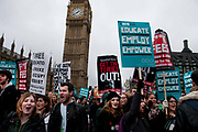 November 21st. Westminster. Demonstration organised by National Union of Students (NUS) against education cuts. A group of students stand shouting in front of Big Ben with placards saying ' Demo 2012. Educate. Employ. Empower' and 'Get the Tories Out'.