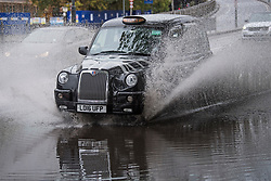 © Licensed to London News Pictures. 03/10/2020. London, UK.  A London black cab ploughs through surface flood water on the A4 eastbound at Hammersmith, west London, as Storm Alex brings heavy rain to large parts of the UK. Photo credit: Ben Cawthra/LNP