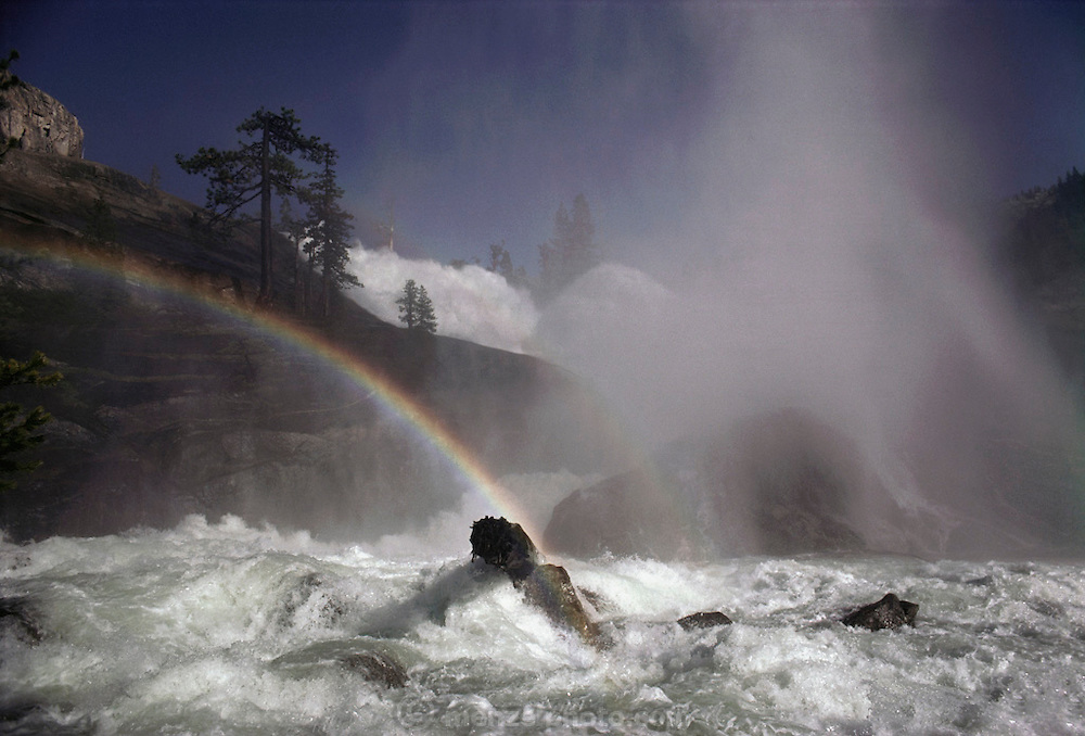 Weather: Rainbow at Waterwheel Falls on the Tuolumne River in Yosemite National Park, California. Rainbows occur when the observer is facing falling rain or mist but with the sun behind them. White light is reflected inside the raindrops and split into its component colors by refraction. (1980)
