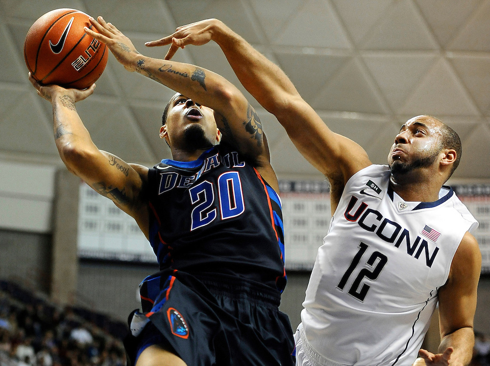 DePaul's Brandon Young (20) is fouled by Connecticut's R.J. Evans (12) as he makes a basket during the first half of an NCAA college basketball game in Storrs, Conn., Tuesday, Jan. 8, 2013. (AP Photo/Jessica Hill)
