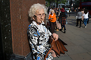 Elderly woman stops to smoke a cigarette while out on Oxford Street which is the busiest shopping district in London, England, United Kingdom.