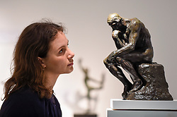 """© Licensed to London News Pictures. 25/06/2019. LONDON, UK. A staff member views """"Le Penseur (The Thinker), Petit Modele"""", conceived in 1881-1882, cast by Alexis Rudier between 1920-1930, by Auguste Rodin at Bowman Sculpture at a preview of Masterpiece London 2019, the world's leading cross-collecting art fair held in the grounds of the Royal Hospital Chelsea.  The fair brings together 157 international exhibitors presenting works from antiquity to the present day and runs 27 June to 3 July 2019.  Photo credit: Stephen Chung/LNP"""