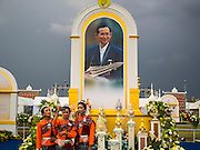 02 DECEMBER 2014 - BANGKOK, THAILAND:  Thai women in traditional attire pose for a selfie in front of a large portrait of Bhumibol Adulyadej, the King of Thailand, after the Trooping of the Colors parade on Sanam Luang in Bangkok. The Thai Royal Guards parade, also known as Trooping of the Colors, occurs every December 2 in celebration of the birthday of Bhumibol Adulyadej, the King of Thailand. The Royal Guards of the Royal Thai Armed Forces perform a military parade and pledge loyalty to the monarch. Historically, the venue has been the Royal Plaza in front of the Dusit Palace and the Ananta Samakhom Throne Hall. This year it was held on Sanam Luang in front of the Grand Palace.   PHOTO BY JACK KURTZ