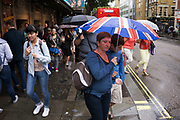 London, UK. Sunday 23rd August 2015. Heavy summer rain showers in the West End. People brave the wet weather armed with umbrellas and waterproof clothing. Union Jack flag umbrella.
