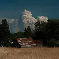 Smoke from a forest fire billows over an old ranch below the Gallatin Range of the Rocky Mountains near Bozeman, Montana.