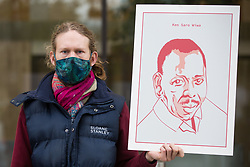 An environmental activist from Extinction Rebellion holds an image of Ken Saro-Wiwa outside the Shell Centre on the 25th anniversary of the killings of the Ogoni Nine on 10 November 2020 in London, United Kingdom. The Ogoni Nine, leaders of the Movement for the Survival of the Ogoni People (MOSOP) including activist Ken Saro-Wiwa, were executed by the Nigerian government in 1995 after having led a series of peaceful marches involving an estimated 300,000 Ogoni people against the environmental degradation of the land and waters of Ogoniland by Shell and to demand both a share of oil revenue and greater political autonomy.