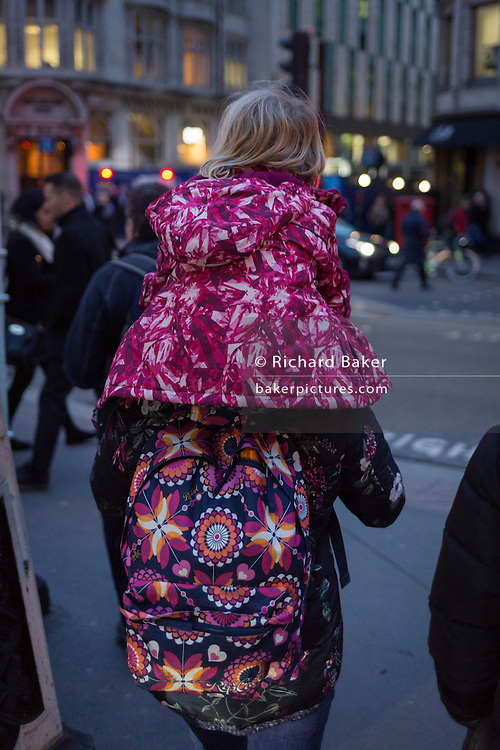 As it becomes dark in the city, a mother carries her child on her shoulders, both wearing clashing patterns on their coats, on 16th February 2017, in the City of London, England.